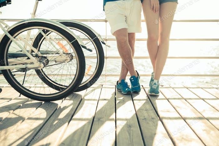 Piernas masculinas y Mujer con bicicleta al aire libre