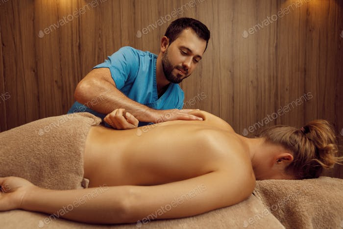 Masseur rubbing back to slim woman with his elbow