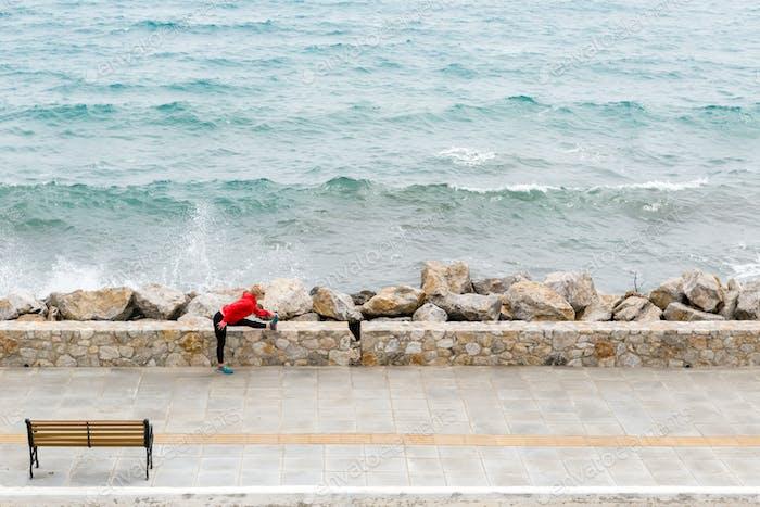 Frau Ausübung und Laufen auf der Stadtstraße, Blick auf Meer