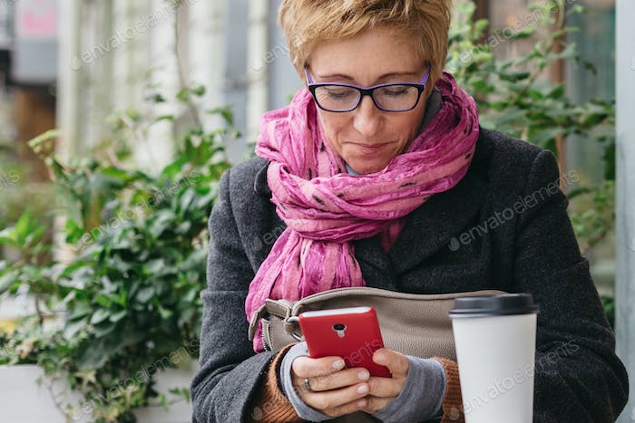 Smiling woman with phone in cafe