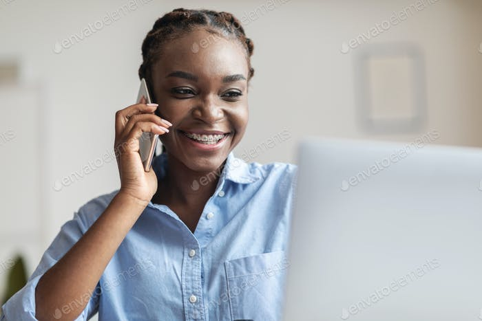 Business Communication. Black Businesswoman Talking On Cellphone And Using Laptop At Workplace