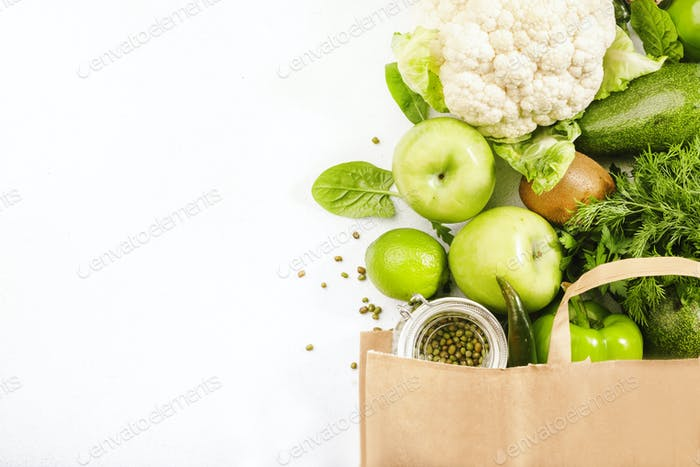 Green vegan food in full paper shopping bag, vegetables and fruits on white