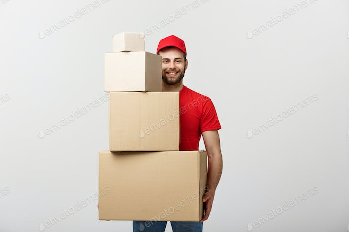 Delivery Concept: Handsome delivery man hold pile cardboard boxes on grey background