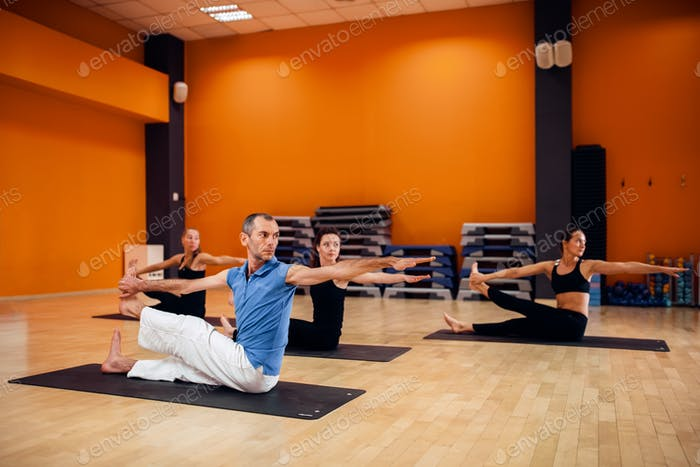 Yoga training, female group workout in gym