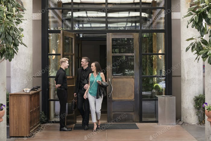 Bellhop abre la puerta para los huéspedes del hotel.
