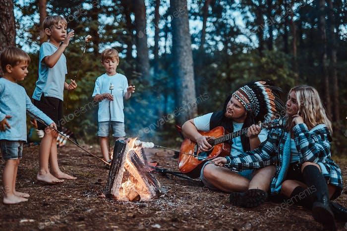 Papi tocando la guitarra para su esposa y sus hijos