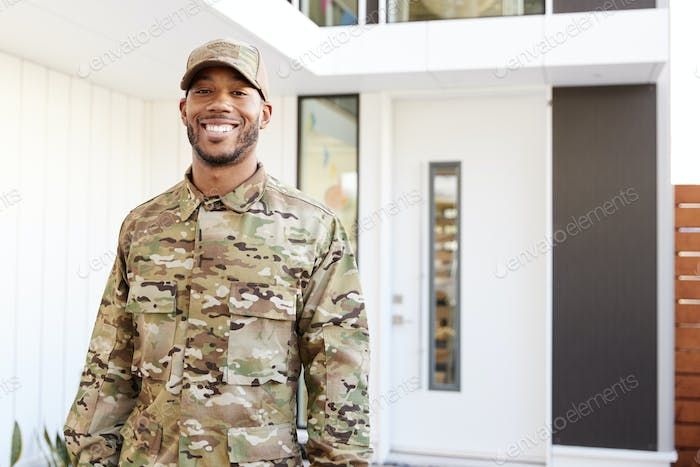 Millennial soldier in camouflage uniform standing outside modern house smiling to camera, close up