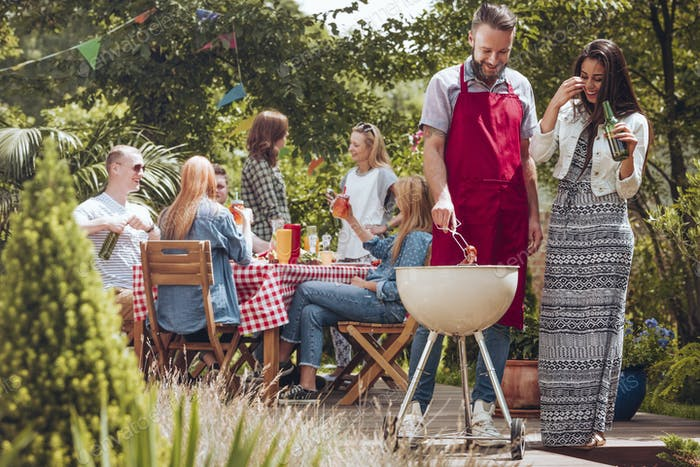 Smiling woman drinking beer while her friend grilling food durin
