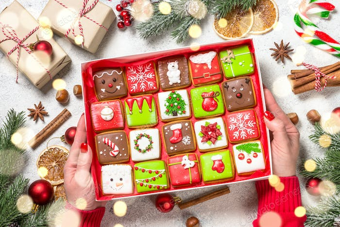 Christmas gingerbread cookies as advent calendar in present box with holidays decorations.