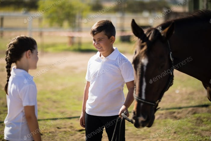 Boy and girl standing with a horse and talking