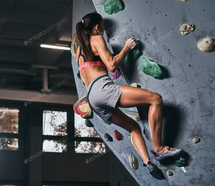 Young woman in shorts and sports bra exercising on a bouldering wall indoors.