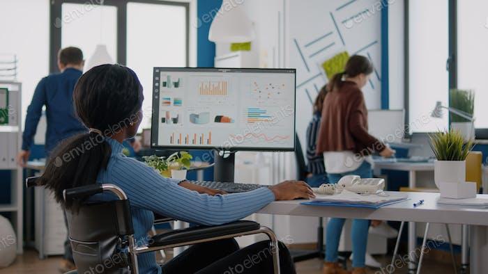 Trabajadora africana con discapacidad analizando información estadística