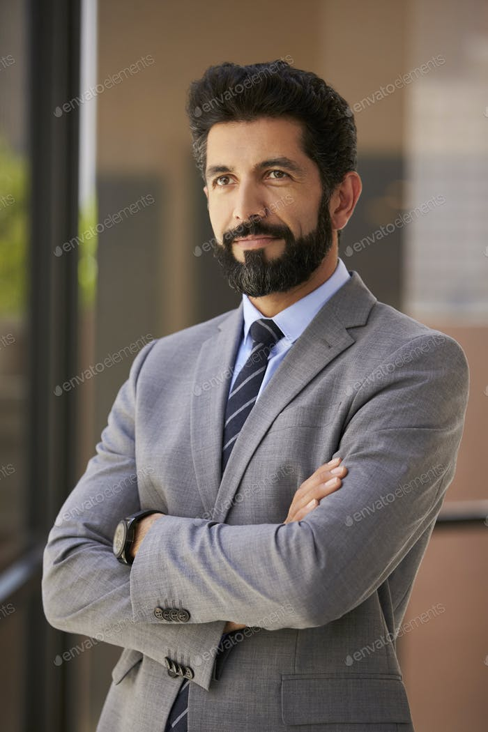Hispanic businessman with arms crossed looks away, vertical
