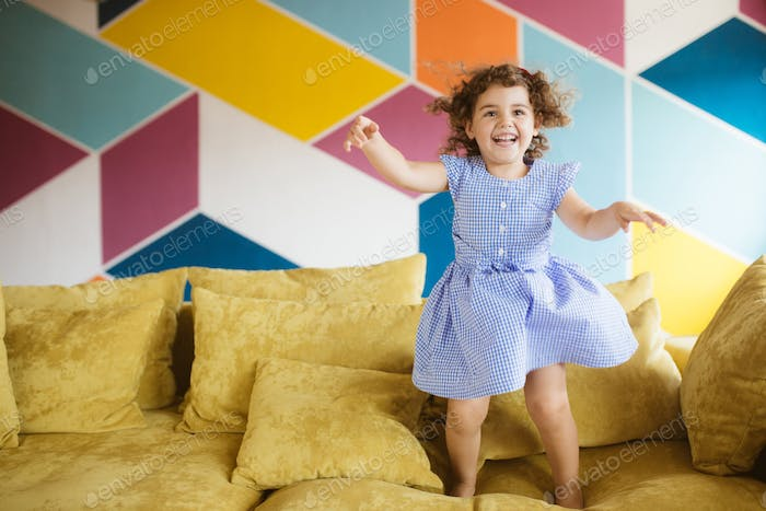 Cheerful little girl with dark curly hair in dress happily jumpi
