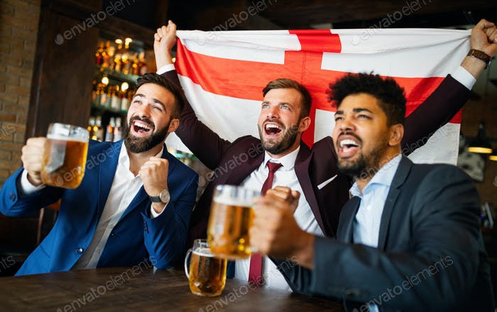 Business men in pub cheering for a sporting event