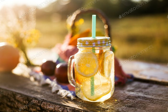 Summer drink in jar and basket with summer fruits in the sun, outdoor picnic or party concept