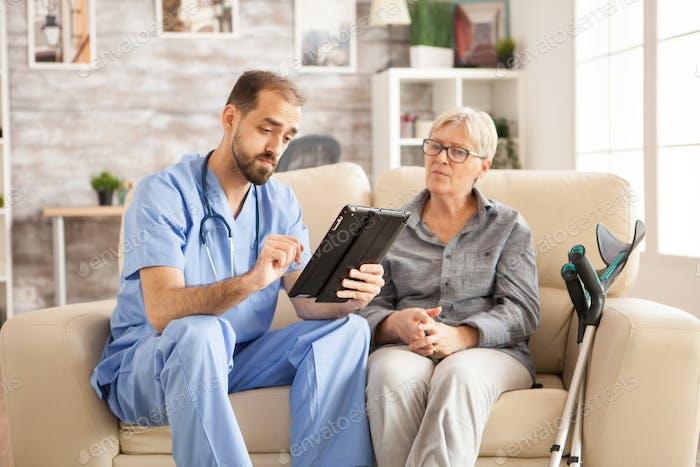 Arzt im Pflegeheim mit Tablet-Computer