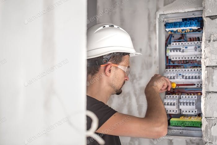 Man, an electrical technician working in a switchboard with fuses.
