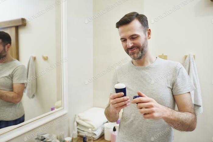 Man applying deodorant to his armpits