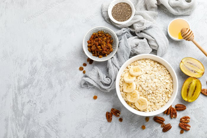 Oat flakes with fruits, nuts and honey in bowl