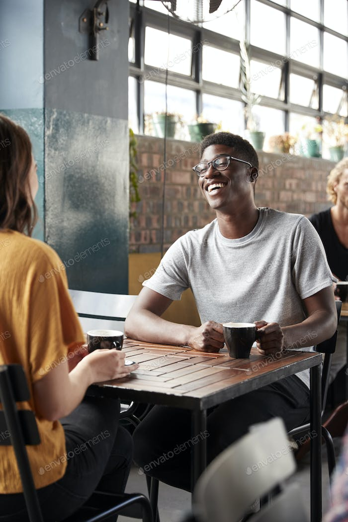 Couple Sitting At Table In Busy Coffee Shop Talking
