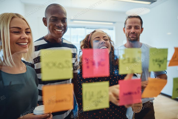 Diverse group of designers laughing during an office brainstorming session