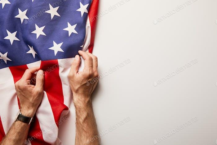 Beschneideansicht des Mannes, der amerikanische Flagge auf weißem Hintergrund mit Kopierraum hält
