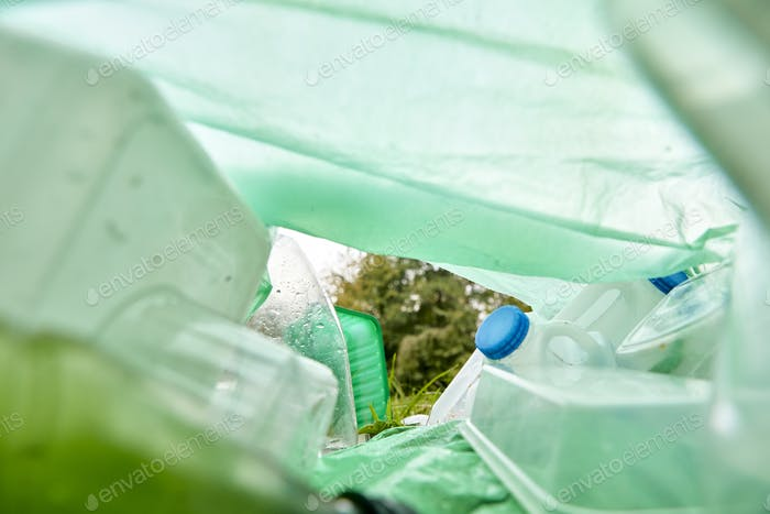 View from inside a plastic bag lying on the grass filled with plastic rubbish