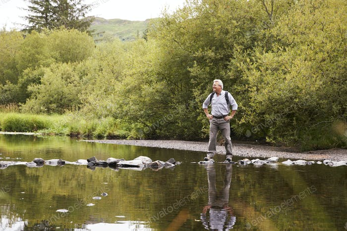 Senior Man Crossing River Whilst Hiking In UK Lake District