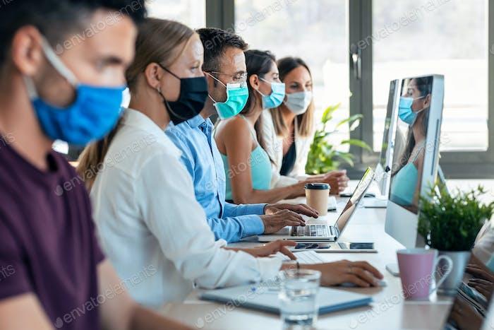 Успешная бизнес-команда носит маску для лица, работая, сохраняя безопасные расстояния на коворкинге.