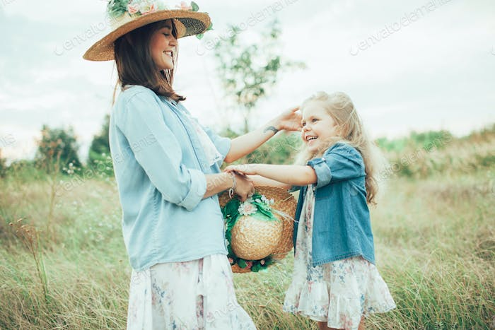 The young mother and daughter on green grass background