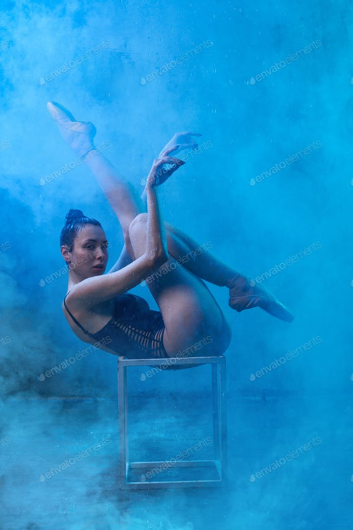 Ballerina stretching on cube in smoke