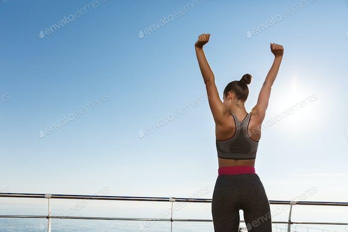 Rückansicht der glücklichen triumphierenden Sportlerin stehend auf einem Pier, die Hände hochheben wie Champion
