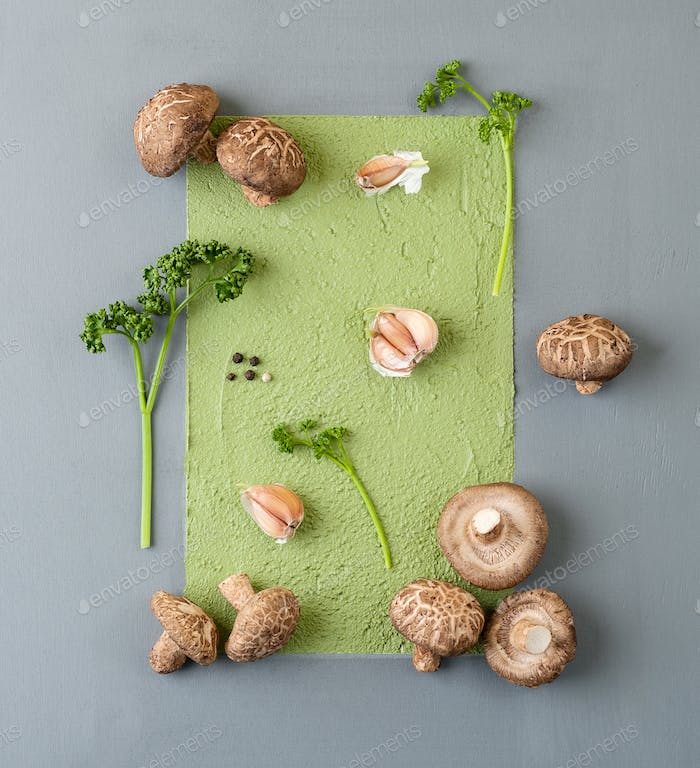 Fresh mushrooms shiitake and stems of curly parsley on an abstra
