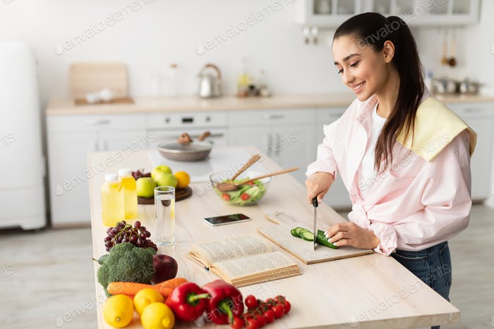 Woman cooking salad and using cookbook at kitchen