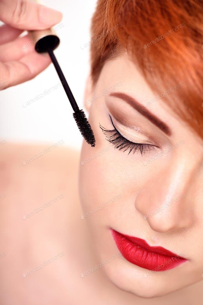 Make-up-Künstler wendet Mascara-Pinsel an. Schöne junge Frau mit
