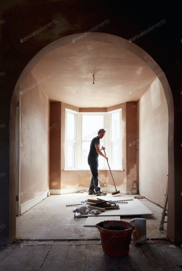 A builder sweeping and tidying up in a renovated replastered house with an archway.
