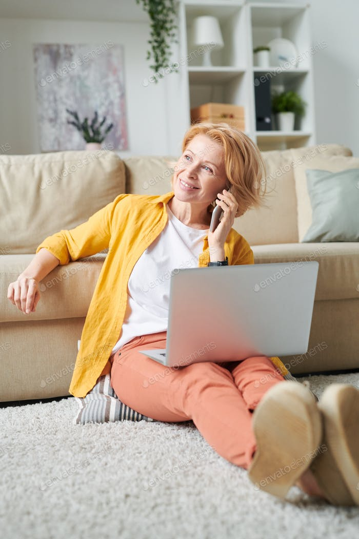 Cheerful mature businesswoman with laptop and smartphone consulting clients