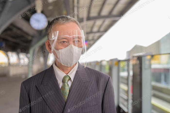 Mature Japanese businessman with mask and face shield waiting at the skytrain station