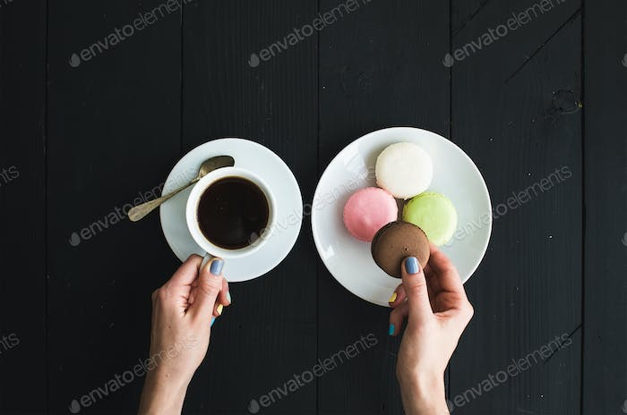 Macaron cookies, cup of espresso and ladie's hands over black wooden backdrop