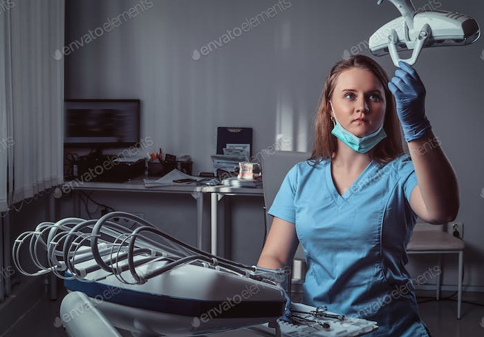 Female dentist adjusting lighting equipment over a chair in the dental clinic.