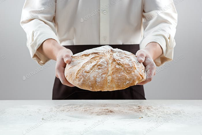 Baker man holding rustic organic loaf of bread in hands