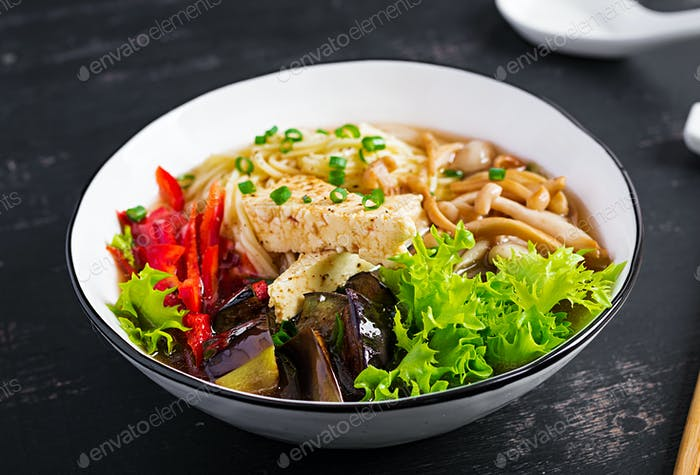 Asian vegan noodles soup with tofu cheese, shimeji mushrooms and fried eggplant