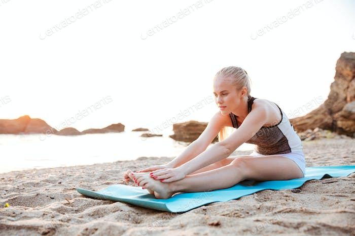 Portrait of a young woman stretching on yoga mat