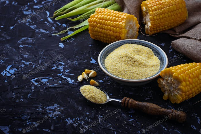 Corn grits and corncob on concrete background