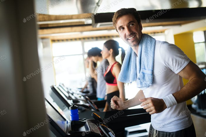 Group of healthy fit people at the gym exercising