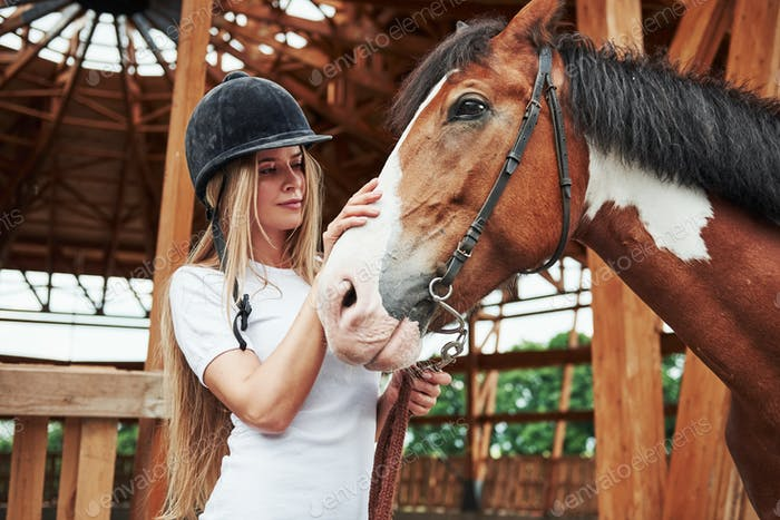 Black mane. Happy woman with her horse on the ranch at daytime