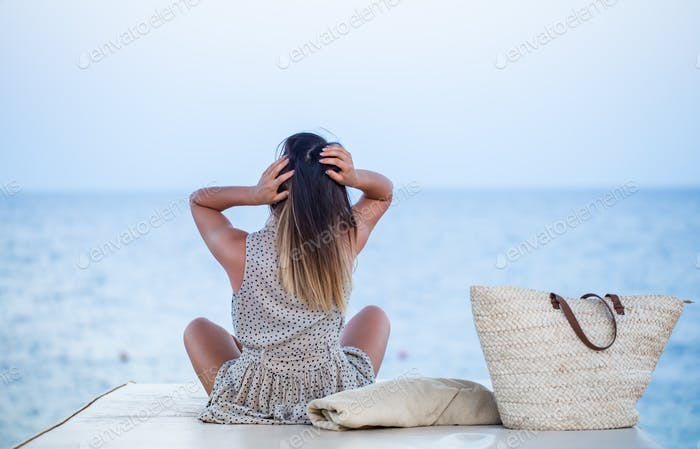 the girl sits by the sea and relaxes