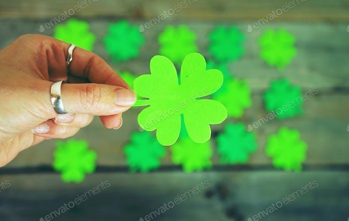 Beautiful close-up of woman hand holds a green irish shamrock wi