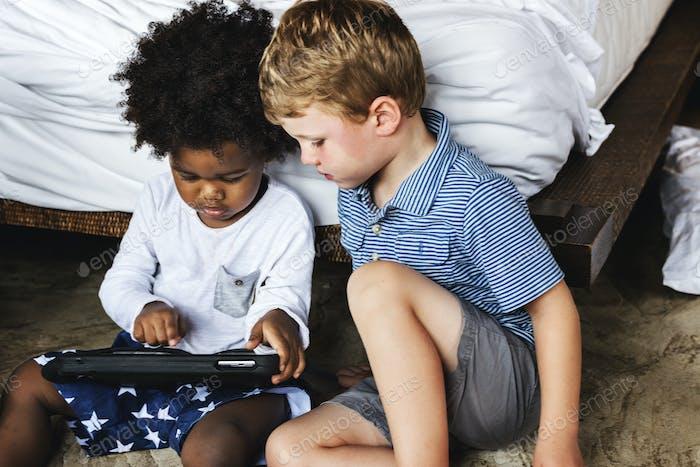 Freunde spielen mit Tablet im Schlafzimmer